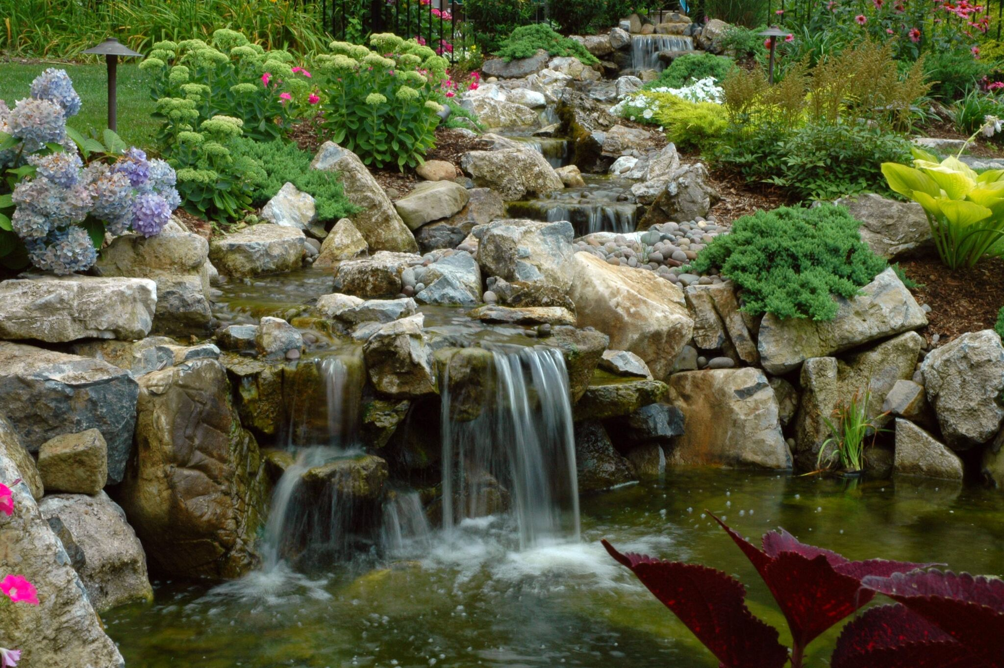 Turning a sloped property into a water side walking trail for Waterfall features for ponds
