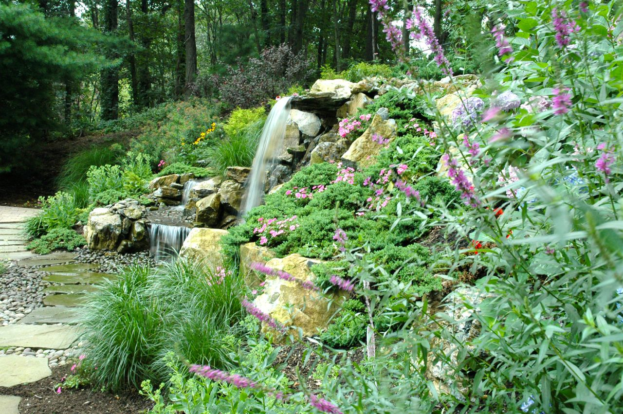 "Natural Retaining Wall with Pondless Waterfall: Here, Deck and Patio used plantings as a key part of a natural retaining wall we built. ""Along with boulders and other rocks, their root systems add to the overall strength of the support system,"" says Dave Stockwell. ""Deck and Patio always chooses plants for their color, bloom periods and how they grow. You can see the river rock we used here instead of concrete or asphalt so that the water seeps through into the reservoir below."