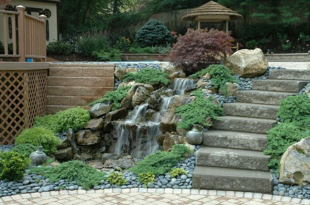 "Walkway Waterfall: Our new ""hardscape"" patio design was tied together with lush, colorful perennials throughout, and at the top of the asphalt walkway we had room to add a new waterfall to create a luxurious and soothing highlight. As you can see from this photo, if you are going ""pondless"" you can fit a waterfall just about anywhere…even between a driveway and upper patio."