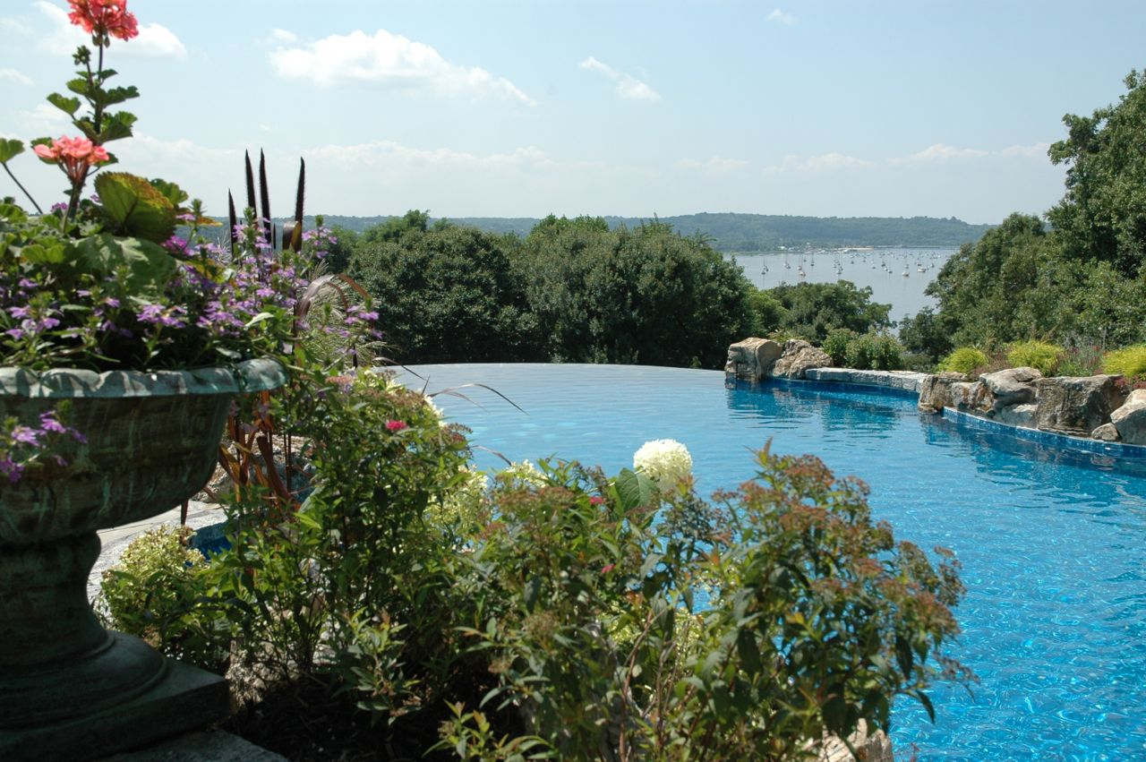 Landscaping Infinity Pool Cove Neck, Long Island: When developing any landscaping plan, it is key to mark out carefully where all the hardscapes will be, as well as any water features. Then you can add in flowering grasses, ground cover, bright plantings in harmony with everything else.