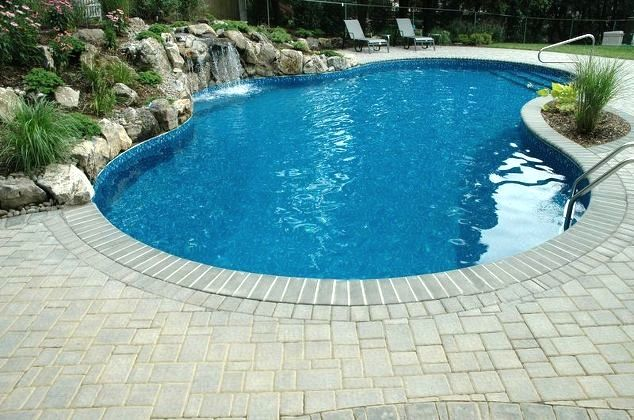 Pool Surround: This pool is surrounded by a patio created from Cambridge's Round Table pavingstones. The pavers' dimpled, embossed surfaces gently roll into soft, beveled edges on four straight-sided Cambridge Shapes with ArmorTec. The pavers were laid in a handsome modified herringbone pattern.