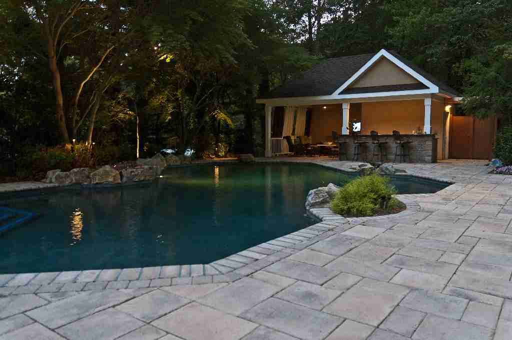 Our outdoor living expert retained and transplanted most of property's original mature growth trees to create a lush setting for pool and cabana area. Resort-style mood of backyard retreat is at its romantic best at sunset.