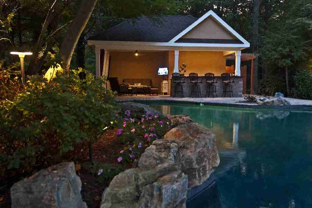 Bright delicate impatiens, moss rock boulders and large mature trees beautifully naturalize original geometric pool area.