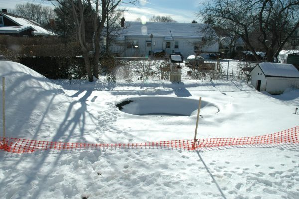 """""""During."""" Winter was upon us not long after we began the project. We did have time to dig out the area for the spa. Then we covered the hole while we all waited for spring to continue."""