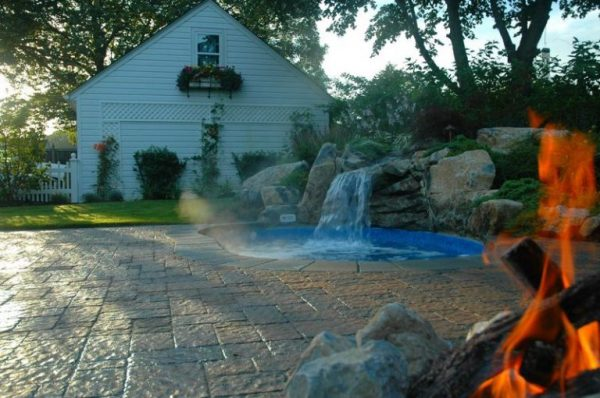 """""""After"""" Landscaping Second angle of """"after"""" job complete. Here you can see the garage, fence, patio and spool; you can almost feel the warmth from their natural gas campfire. The end result is a beautiful backyard oasis tucked nicely into a corner of their new backyard patio."""