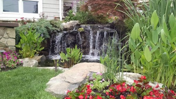 Not all waterfall projects need to be on a grand scale. Even modest projects such as this is an opportunity for natural color, textures, and pleasant sounds. Waterfalls splashing in a pond aerates it, keeping it healthy and mosquito-free. Add some boulders and bright lush plantings and you have a little bit of paradise.