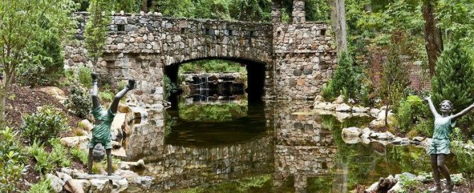 Large Reflecting Pond with Stone Bridge (Long Island/NY): The stone bridge with turret creates a stunning pond reflection in its crystal clear water. The water stays this way because we used a natural ecosystem to keep it clean. There is a large bog filter at the waterfall on one end, with a 3,000 gallon pondless reservoir with two 20,000 GPH pumps feeding the waterfall.