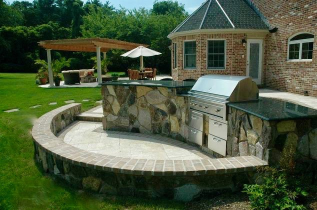 Travertine Patio/Outdoor Kitchen: Close to the outdoor living room and dining area is the client's bar/barbecue. With a natural stone veneer, an semi-circular seat wall with the same veneer offers extra seating when entertaining.