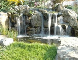 Backyard Water Feature by Deck and Patio