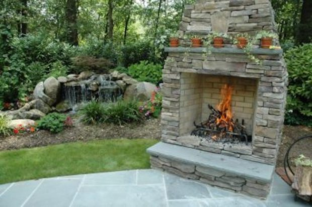 Stand-alone fireplace at the edge of a patio: