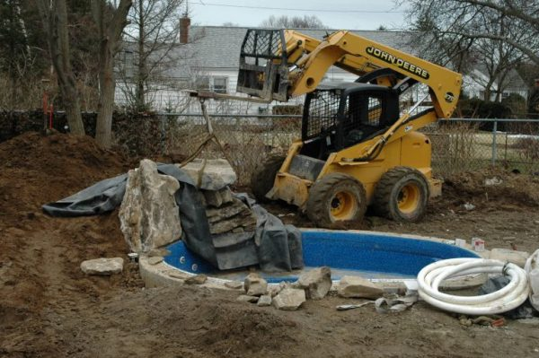 """""""During"""" Waterfall Addition: The huge boulders required for a natural-looking waterfall can weigh tons and special machinery is needed to put them in place."""
