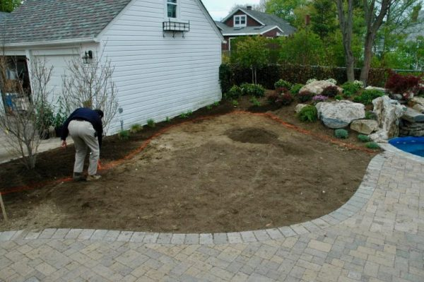 'Before' Landscaping: Here a member of our team is marking out the landscaping areas for behind the waterfall up to the garage. You can see (on the right) the spool and waterfall are already complete. You can also see a small segment of the new patio.