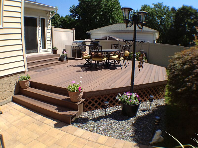 """Fiberon Protect Advantage Cedar Capped Composite Decking: Planters are a budget-friendly way to add bursts of color around the deck. You can even grow vegetables in planters such as a """"summer salad"""" container for tomatoes and cucumbers."""
