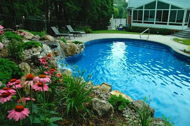 Free-form Vinly Pool: Vinyl-lined pools can be constructed in any shape, curve, or angle, which made it easier to fit a pool in this yard. By taking advantage of the property's rising grade, Deck and Patio created a natural retaining wall, studded with gorgeous plantings, moss and river rock to hold back the rising soil. Added benefit: the sounds an added waterfall makes their long desired pool experience even better.
